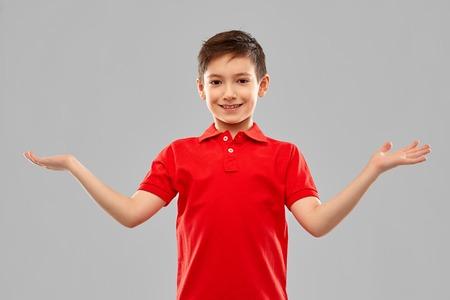smiling boy holding something on empty hands Stock Photo