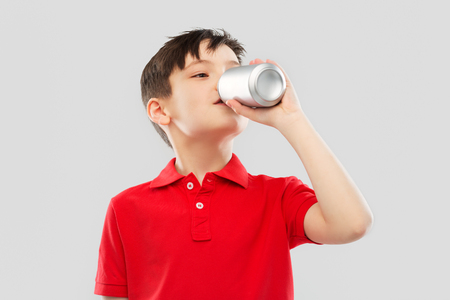 boy in red t-shirt drinking soda from tin can Standard-Bild