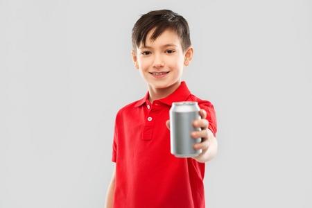Junge im roten T-Shirt trinkt Soda aus der Blechdose Standard-Bild