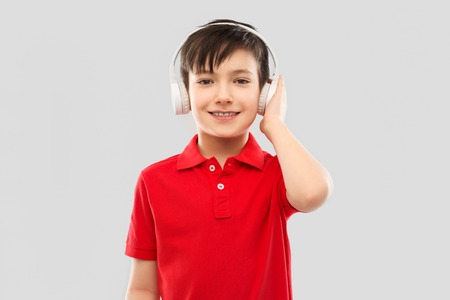 smiling boy in headphones listening to music