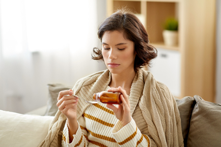 sick woman with antipyretic or cough syrup at home