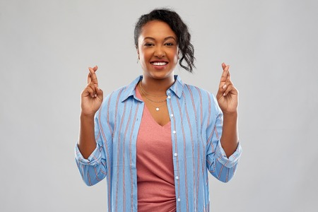 african american woman holding fingers crossed