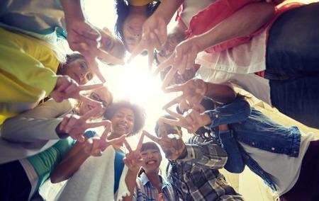 Onderwijs, vriendschap, gebaar, overwinning en mensenconcept - Groep gelukkige internationale studenten of vrienden die in cirkel staan en vrede of v-teken tonen Stockfoto