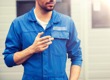 Service, repair, maintenance and people concept - Close up of auto mechanic smoking cigarette