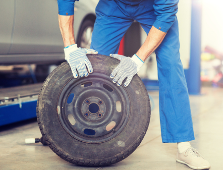 Car service, repair, maintenance and people concept - Auto mechanic man with wheel tire at workshop