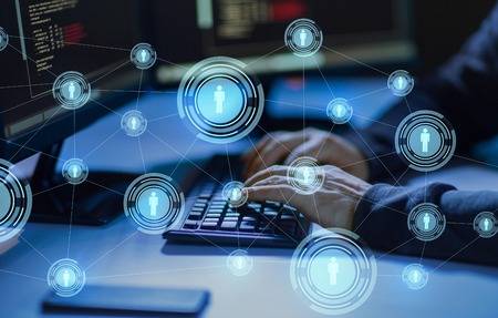 Cybercrime, hacking and technology concept - Hands of hacker in dark room writing code or using computer virus program for cyber attack