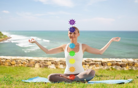 Mindfulness, spirituality and outdoor yoga - Woman meditating in lotus pose with seven chakra symbols over ocean in french polynesian background Imagens