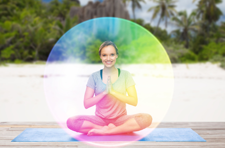Mindfulness, spirituality and outdoor yoga - Woman meditating in lotus pose with rainbow aura over Seychelles island beach background Imagens