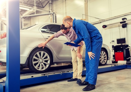 Auto service, repair, maintenance and people concept - Mechanic with clipboard and man or owner at car shop 版權商用圖片 - 120888881
