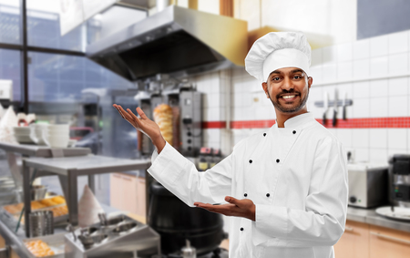 Cooking, profession and people concept - Happy male Indian chef in toque presenting something over kebab shop kitchen background