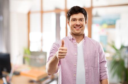 Gesten- und Personenkonzept - Glücklicher junger Mann, der Daumen über Büroraumhintergrund zeigt Standard-Bild