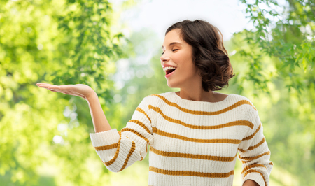 People concept - Happy smiling young woman in striped pullover holding something imaginary on empty palm over green natural background