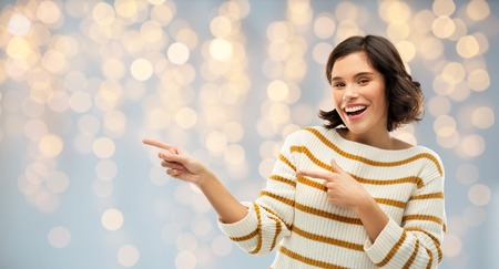 People concept - Happy smiling young woman in striped pullover pointing fingers to something over festive lights background