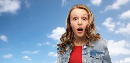Emotion, expression and people concept - Surprised or shocked teenage girl with open mouth over blue sky and clouds background Stock Photo