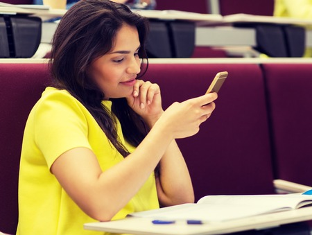 Education, high school, university, learning and people concept - Student girl with smartphone on lecture Stock fotó