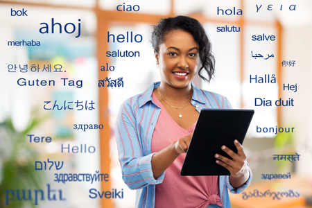 Technology, translation and people concept - Happy African American woman using tablet computer over greeting words in different foreign languages