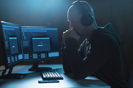 Cybercrime, hacking and technology concept - Male hacker in headphones with progress loading bar on computer's screens wiretapping or using computer virus program for cyber attack in dark room Stock Photo
