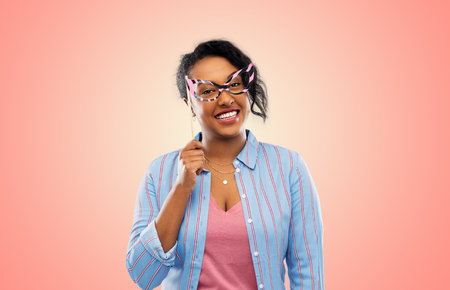 Party props, photo booth and people concept - Happy African American young woman with big glasses over living coral background Stock Photo