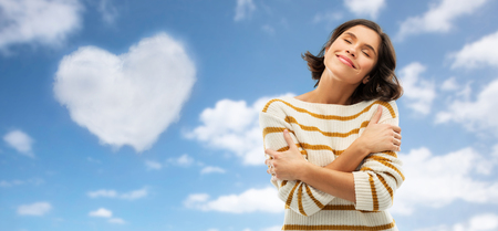 Valentines day, love people concept - Happy pleased young woman in striped pullover with closed eyes hugging herself over blue sky and cloud in shape of heart background
