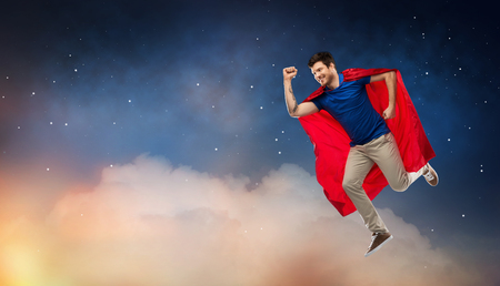 Super power and people concept - Happy young man in red superhero cape flying in air over starry night sky background Imagens