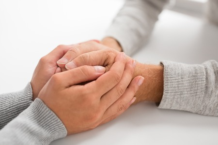 Old age, family, care and support concept - close up of young woman holding senior man hands Zdjęcie Seryjne