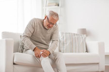 Concepto de personas, atención médica y problema: hombre mayor infeliz que sufre de dolor de rodilla en casa Foto de archivo