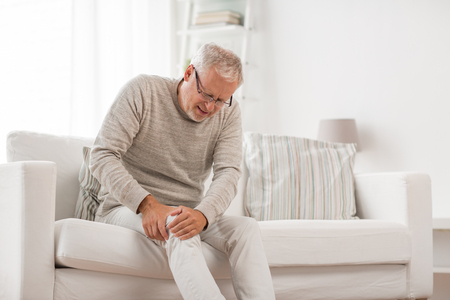 People, health care and problem concept - unhappy senior man suffering from knee ache at home Stockfoto
