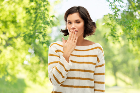People concept - happy smiling young woman in striped pullover covering mouth by hand and giggling over green natural background Reklamní fotografie
