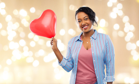 Valentines day and people concept - happy African American young woman with red heart-shaped balloon over festive lights on beige background
