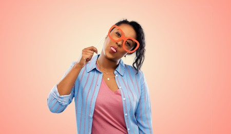 Party props, photo booth and people concept - happy African American young woman with big glasses showing tongue over living coral background