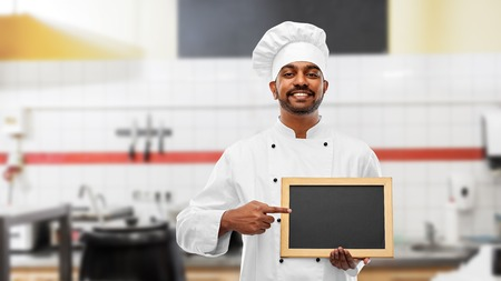Cooking, profession and people concept - happy male Indian chef in toque with blank chalkboard for menu over restaurant kitchen background Imagens