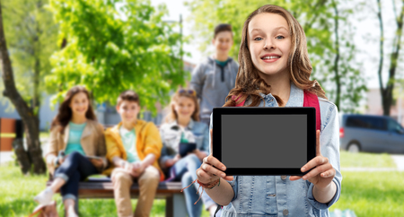 Education, school and people concept - happy smiling teenage student girl with bag showing blank tablet computer screen over group of friends outdoors background