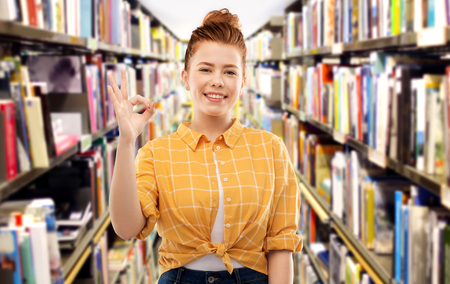 Gesture and people concept - smiling red haired teenage student girl in checkered shirt showing ok hand sign over library background
