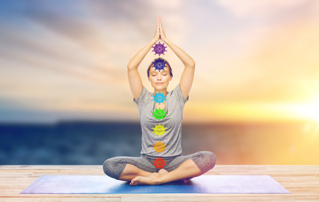 Mindfulness, spirituality and outdoor yoga - woman meditating in lotus pose with seven chakra symbols over sea and sunlight background Imagens