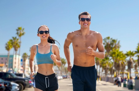 Fitness, sport and lifestyle concept - happy couple in sports clothes and sunglasses running over Venice beach background in California