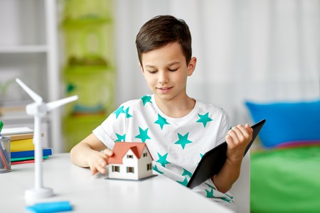 Ecology, technology and energy saving concept - smiling boy with tablet pc computer, toy house model and wind turbine at home Imagens