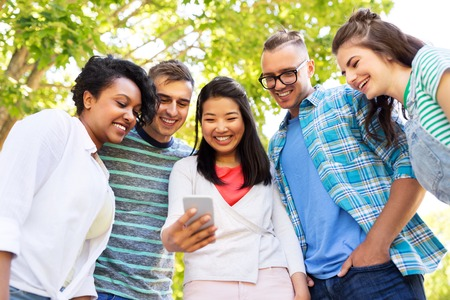 Friendship, technology and international concept - group of friends with smartphone at summer park