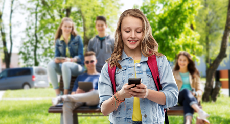Education, school and people concept - happy smiling teenage student girl with bag and smartphone over group of friends background