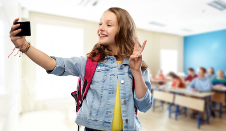 Education, school and people concept - happy smiling teenage student girl with bag taking selfie by smartphone and showing peace over classroom background Imagens