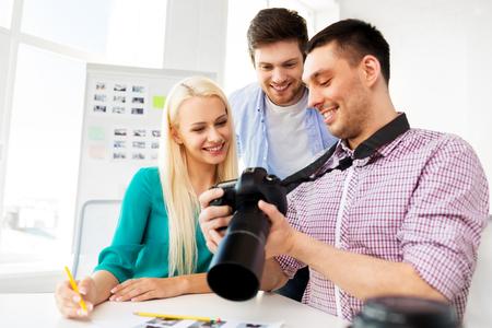 Concepto de fotografía y gente creativa - fotógrafos con cámara en estudio fotográfico