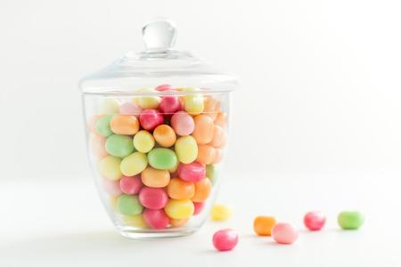 Concepto de alimentos, confitería y dulces - frasco de vidrio con gotas de caramelo de colores sobre fondo blanco.