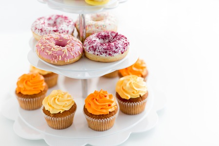 Fast food and sweets concept - glazed donuts and cupcakes with buttercream frosting on stand over white background