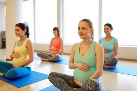Pregnancy, fitness and healthy lifestyle concept - group of happy pregnant women exercising in lotus pose at gym yoga Imagens