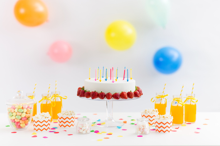 Party food and festive concept - birthday cake with candles and strawberries, drinks, popcorn and marshmallow on table