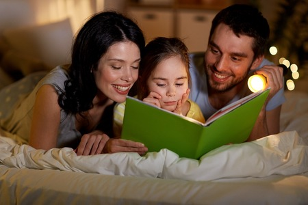 People and family concept - happy mother, father and little daughter reading book with torch light in bed at night at home