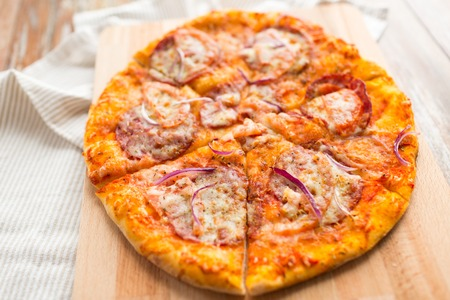 Food, culinary and eating concept - close up of sliced homemade pizza on wooden table
