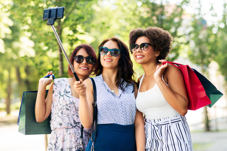 Sale, friendship and technology concept - happy young women with shopping bags taking selfie by smartphone in outdoors