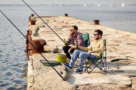 Leisure and people concept - happy friends fishing and drinking beer on pier Imagens