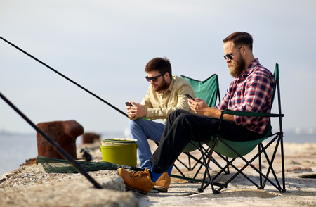 Leisure and people concept - friends with smartphones fishing on pier at sea Imagens