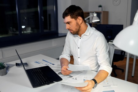 Business, deadline and stress concept - businessman with papers and laptop computer working at night office